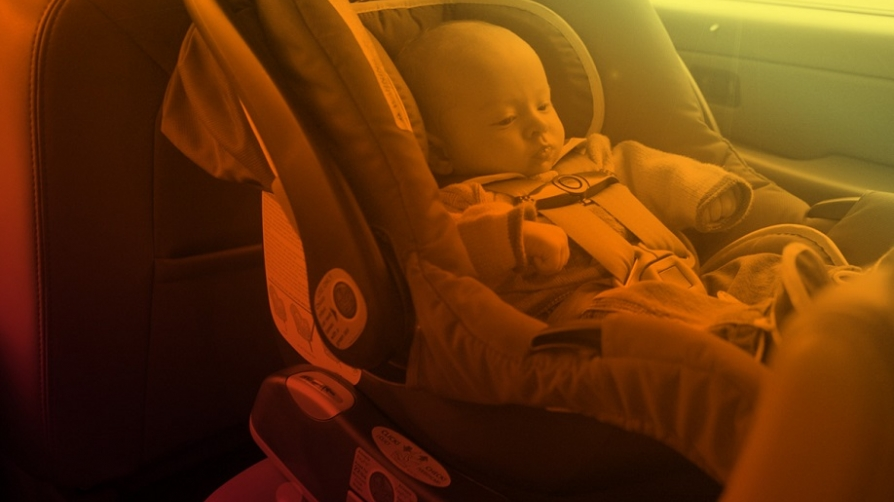 Baby in the back seat of a car in a car seat.