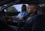 Two men in a vehicle wearing seat belts