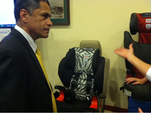 Photo of F.H.W.A. Administrator Mendez learning about child safety seats