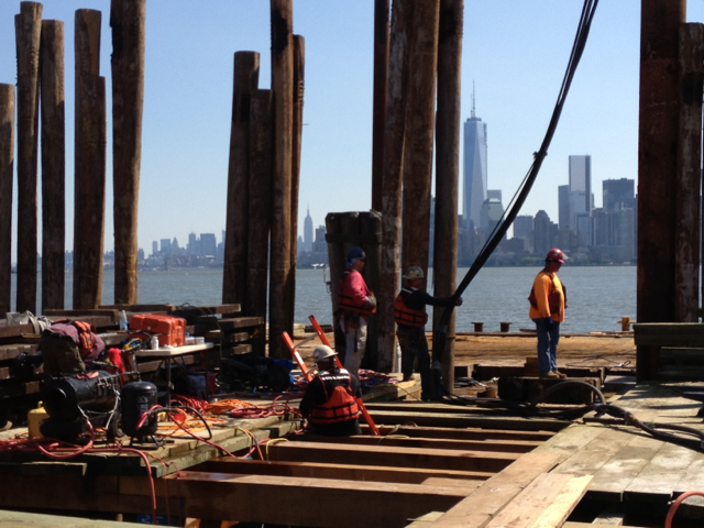 Photo of crews working on Liberty Island docks with downtown Manhattan skyline in background