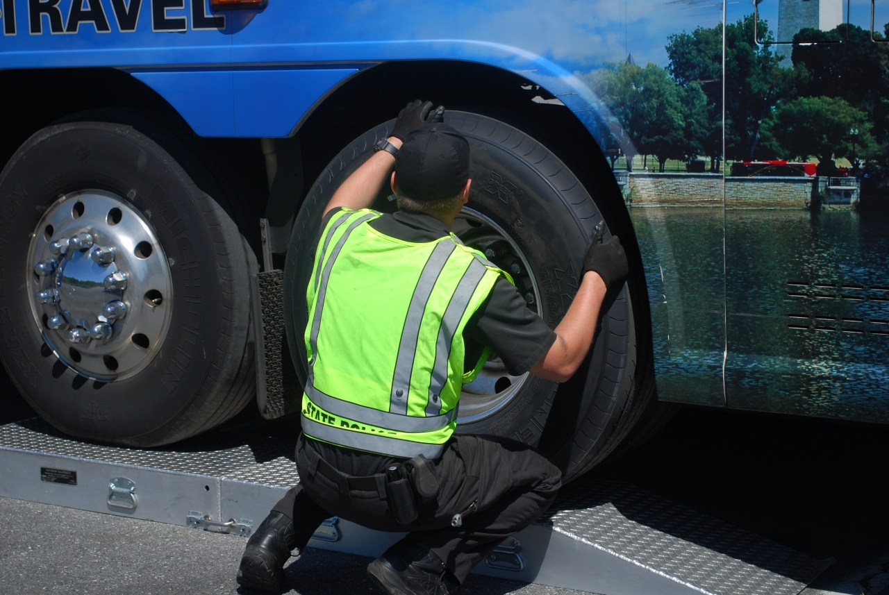 Photo of investigator inspecting motorcoach wheels