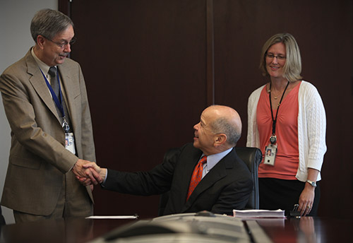 Photo of FAA Administrator Michael Huerta shaking hands with John Duncan, Deputy Director of Flight Standards, as Barbara Adams with Flight Standards, looks on after Administrator Huerta signed the Pilot Qualification Rule