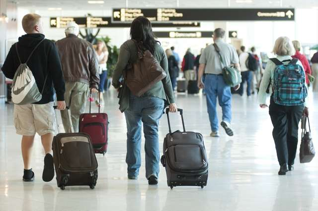 Photo of travelers moving through airport