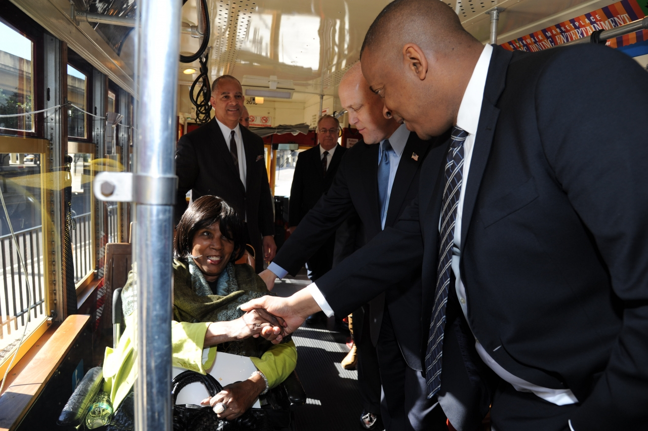 Photo of Secretary Foxx greeting a passenger on the Loyola Streetcar line