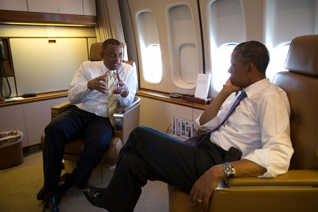 Official White House photo of Secretary Foxx talking with President Obama aboard Air Force One enroute to Jacksonville