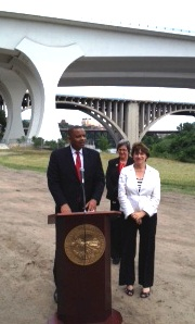 Photo of Secretary Foxx speaking with new I-35W Bridge in the background