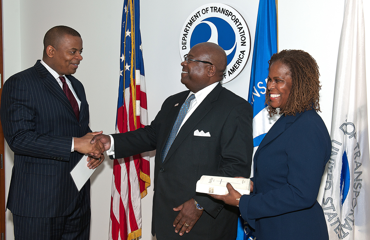 Photo of Secretary Foxx swearing-in Administrator Winfree as his wife holds a Bible