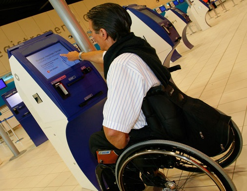 Passenger in wheelchair uses airport kiosk