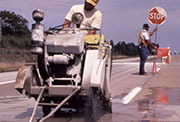 Man holding stop sign on roadway in background while man in foreground is doing roadwork.