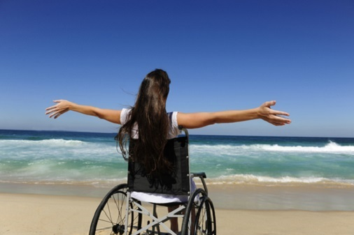Photo of woman in a wheelchair on a beach celebrating her access to the ocean
