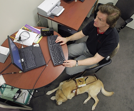 Photo of man at computer with service dog by his side