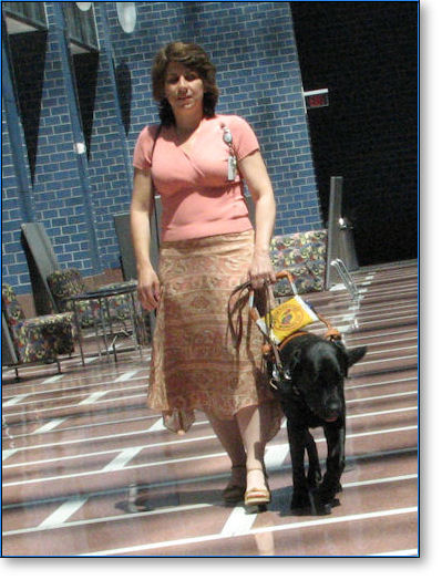 Woman walking with black guide dog in sunny atrium
