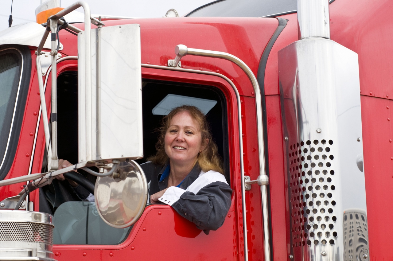 Woman sitting in the cab of a red tractor trailer cab