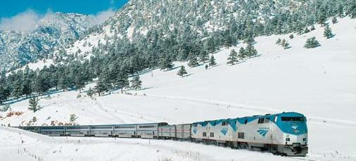 Amtrak train passing by snowy mountains
