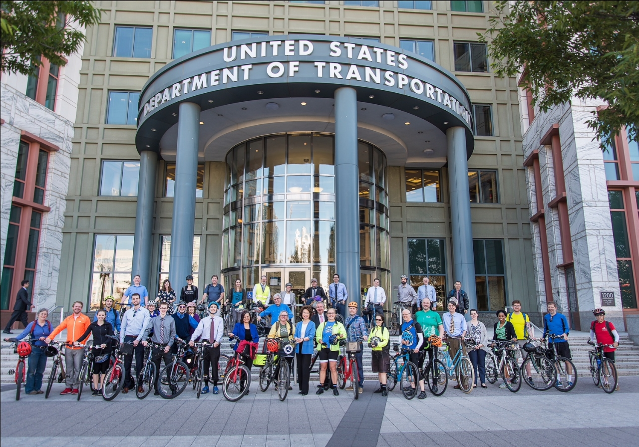 Secretary Chao poses with cyclists infront of DOT Headquarters