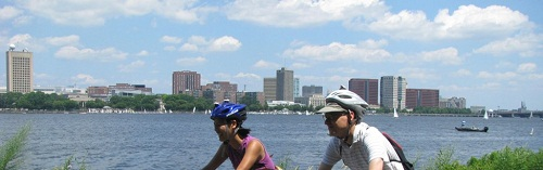 two people riding bikes along a river's edge on a bike path