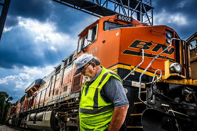 Photo of a freight train and worker in a rail yard
