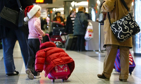 Photo of young girl with Santa hat at airport