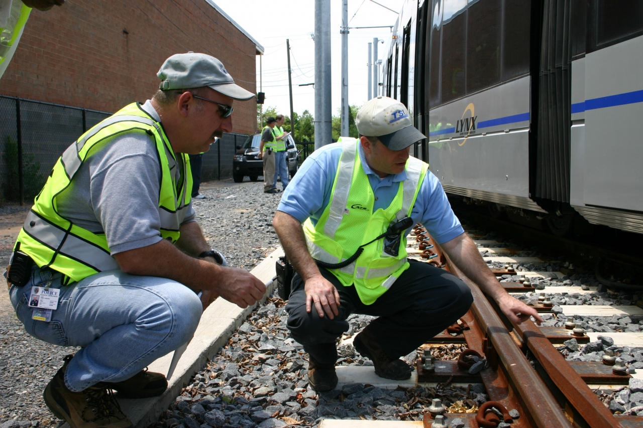 Photo of two TSI employees squatting and inspecting a train and rail