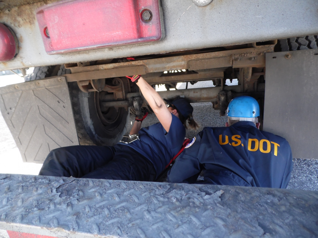Photo of DOT inspectors under a truck