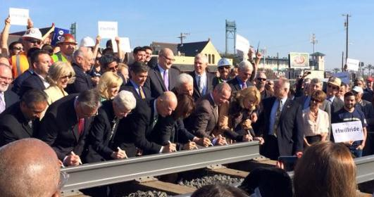 Photo of guests signing the first rail at high speed rail track laying