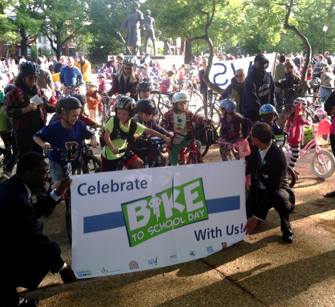 Victor Mendez (right) holds bike-to-school day banner