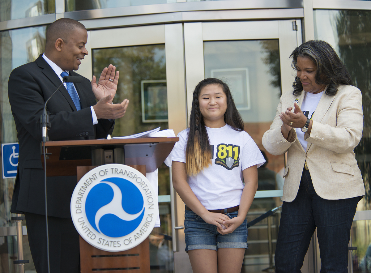 Photo of Secretary Foxx and PHMSA Administrator Cynthia Quarterman with 811Poster Contest winner