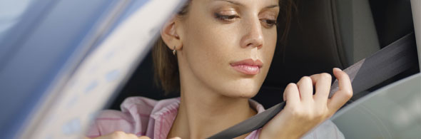 Photo of young woman driver putting on seat belt