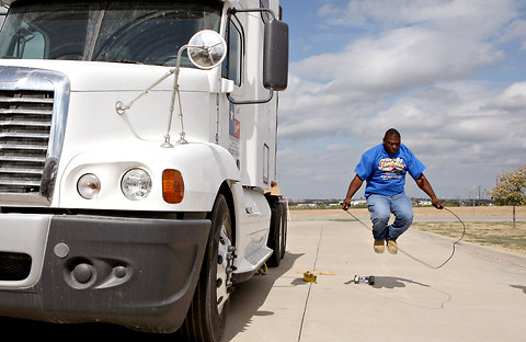 Photo of a trucker doing jumprope exercises outside his rig