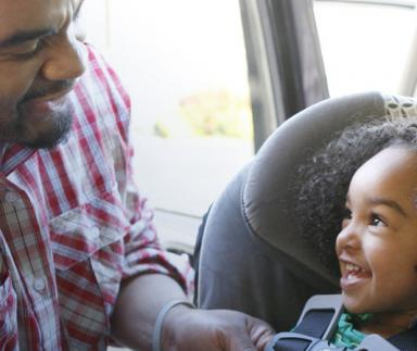 A father buckles a car-seat.