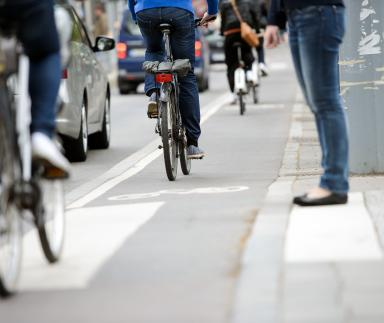 A pedestrian stops for a bicycle.