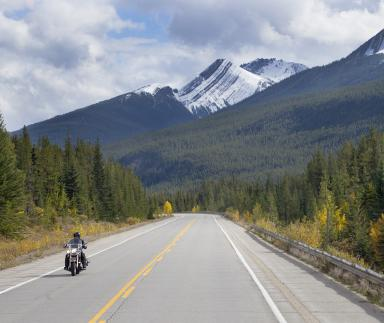 A motorbike is ridden with a mountainous backdrop.