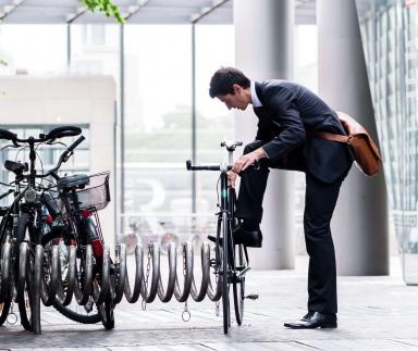 A suited man locks his bike up.