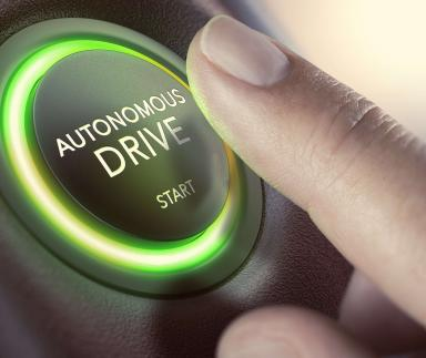 A finger pushes an autonomous start button.