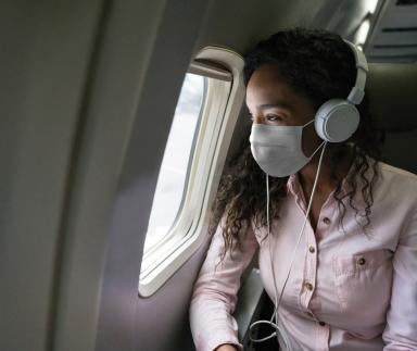 Passenger with a mask next to aircraft window.