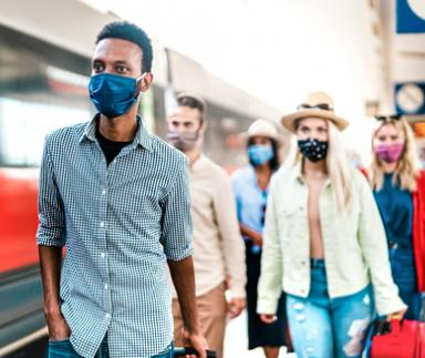 People walking on a subway platform with masks on