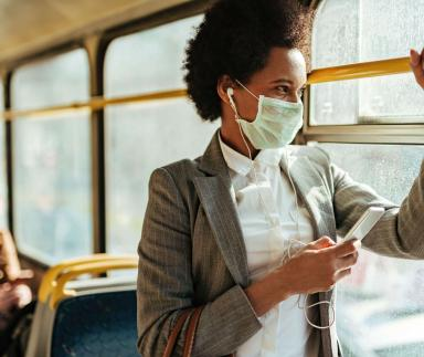 A woman wears a mask while riding a bus.