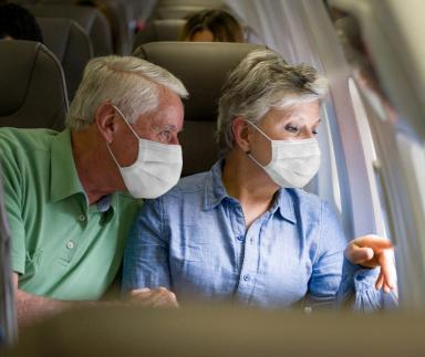 Elderly travelers with masks look out airplane window