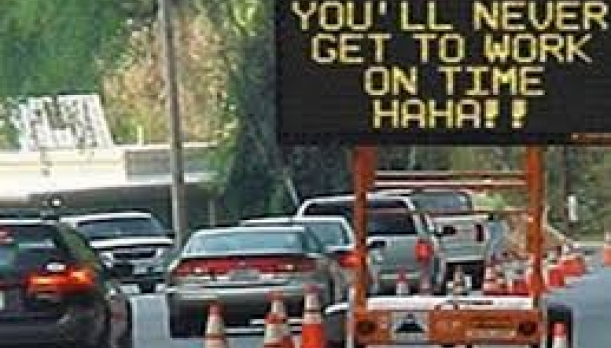 """Hacked Road Sign Saying """"You'll never get to work on time HAHA!"""""""