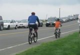 Photo of adult and child riding bicycles in a narrow bike lane