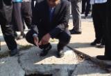 Photo of Secretary Foxx examining a hole in Kansas City sdiewalk